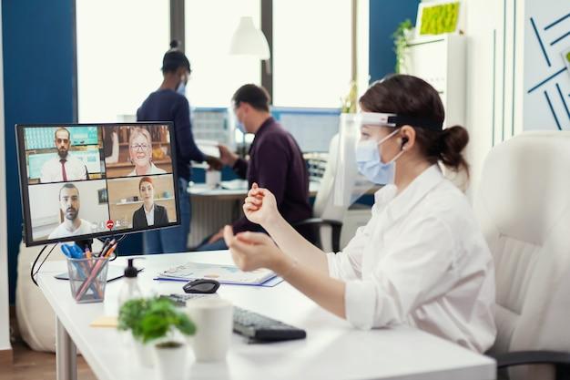 사업가는 직장에서 컴퓨터로 온라인 회의를 하는 동안 사업가들을 듣고 얼굴 마스크를 쓰고 있습니다. 동료들이 사회적 거리를 존중하면서 일하는 동안 화상 통화를 하는 기업가
