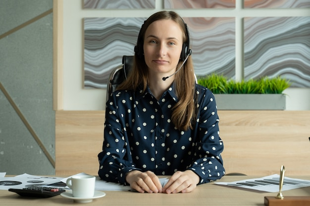 Деловая женщина смотрит и разговаривает через веб-камеру во время видеоконференции из офиса