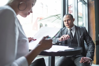 Businesswoman looking at his colleague examining document in caf�