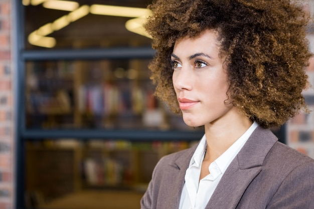 Businesswoman looking away and thinking in office
