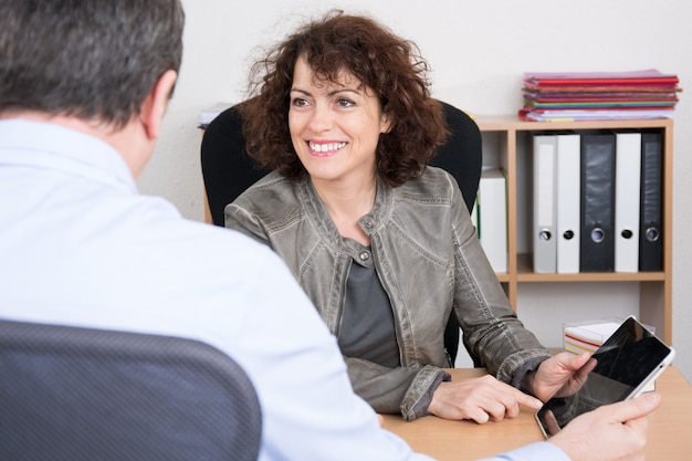 Businesswoman looking at businessman at office desk