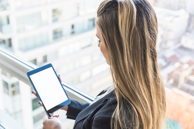 Businesswoman looking at digital tablet with white display screen