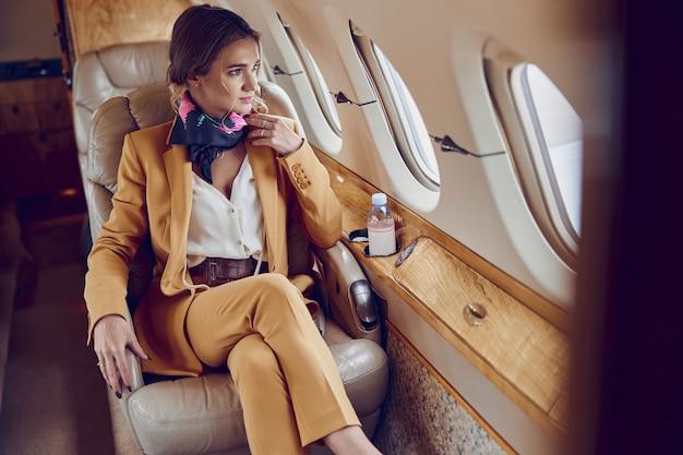 プライベート飛行機のジェット機で窓から見ている実業家。現代の旅客機。若いヨーロッパの女性はフォーマルなスーツを着ています。民間商用航空。空の旅とビジネスの概念
