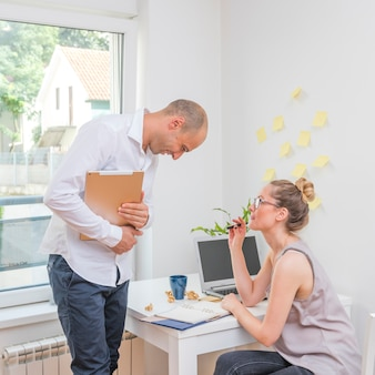 Businesswoman looking at her partner checking schedule in diary