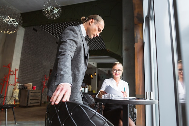 Businesswoman looking at her partner sitting on chair in caf�