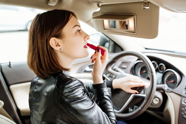Businesswoman looking in rear view mirror and making up her lips with red lipstick in car