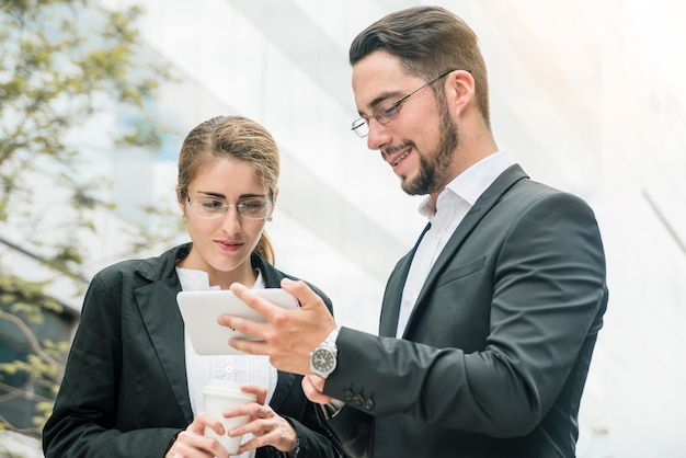 Businesswoman looking at smartphone hold by a smiling young businessman