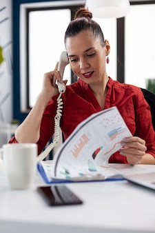 Businesswoman looking through finance charts on clipboard