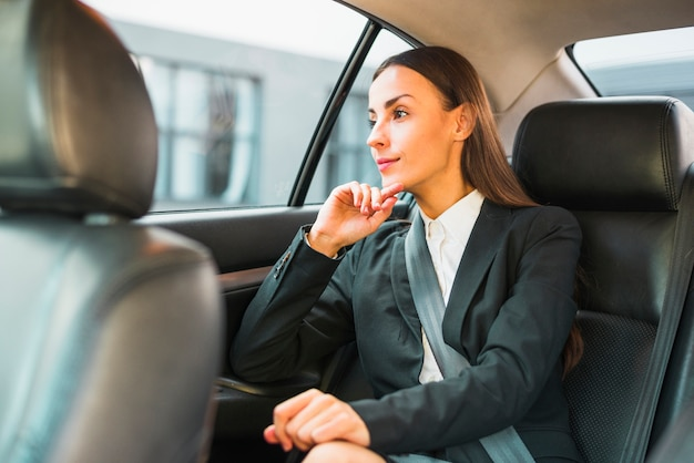 Businesswoman looking through window while traveling by car