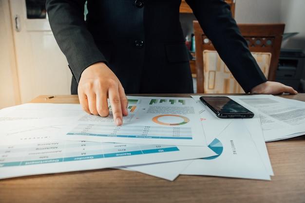 Предприниматель ищет оборот компании со многими документами на своем столе и указывая