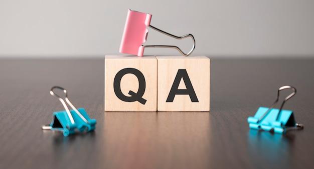 사업가는 나무 빌딩 블록으로 단어 qa를 만들었습니다.