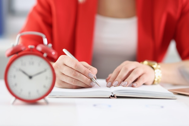 Businesswoman makes notes in documents there is an alarm clock next to it