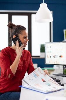 Businesswoman making a call using smartphone sitting at desk Free Photo