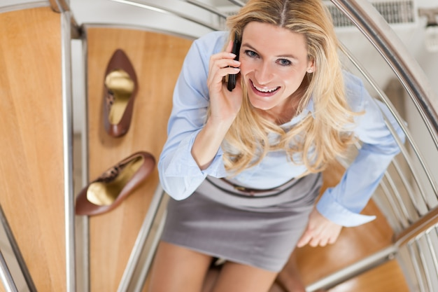 Businesswoman making a phone call at home