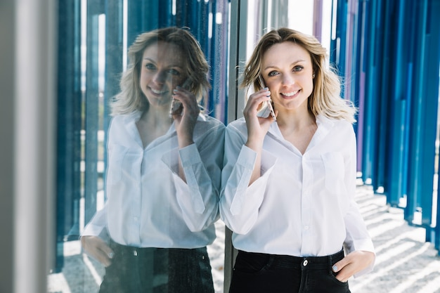 Businesswoman making phone call next to windows