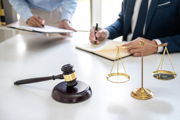 Businesswoman and male lawyer or judge consult and conference having team meeting with client at law firm in office, law and legal services concept. Premium Photo