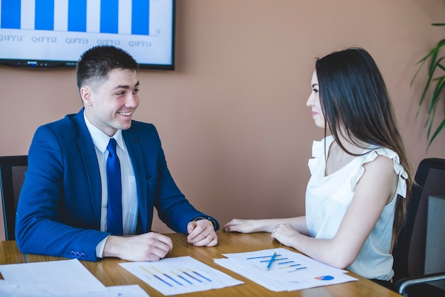 Businesswoman and man sitting at table