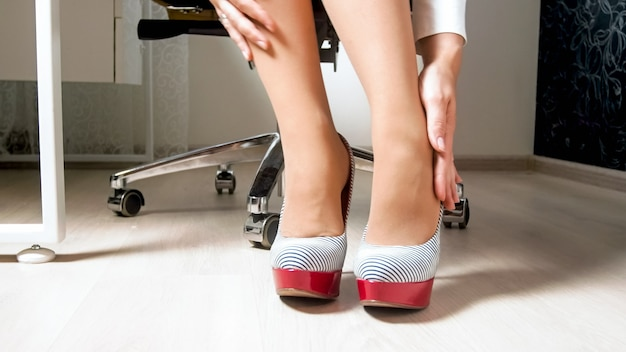 Businesswoman massaging aching legs and feet after wearing high heels shoes in office.