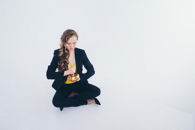 Предприниматель медитации. приготовление зелья на белом. поющая чаша с буддийской мантрой в руке женщины в костюме