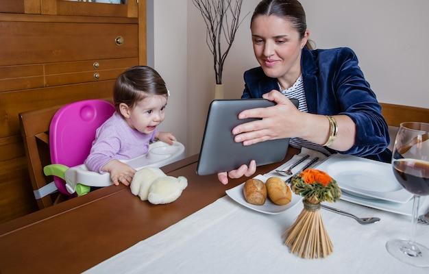 레스토랑 테이블에 앉아 태블릿 컴퓨터를 찾고 사업가 어머니와 행복한 아기 소녀