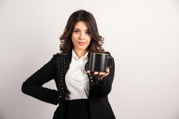 Деловая женщина, предлагающая чашку чая на белом
