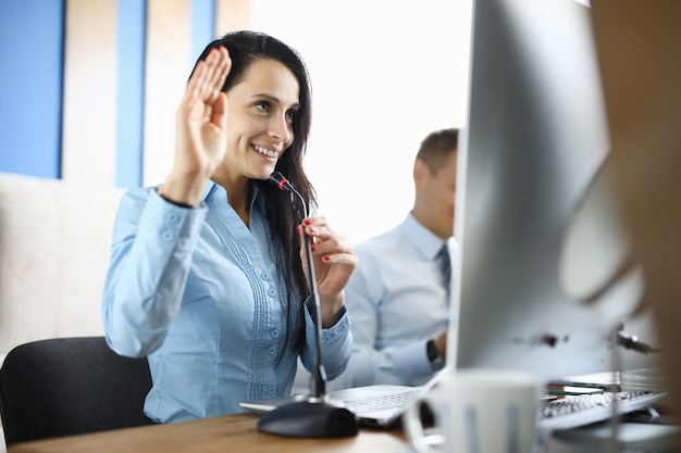 Businesswoman in office holds microphone and greets interlocutor for online communication.
