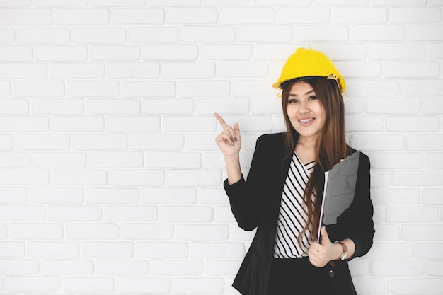 Businesswoman in office with hard hat and clipboard