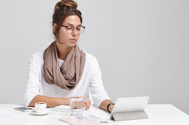La donna di affari in ufficio lavora sulla tavoletta digitale, guarda seriamente.
