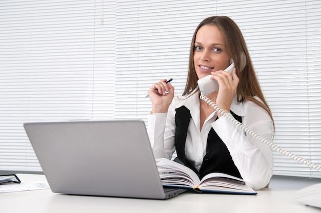 電話で実業家が彼女のオフィスでカメラに見える