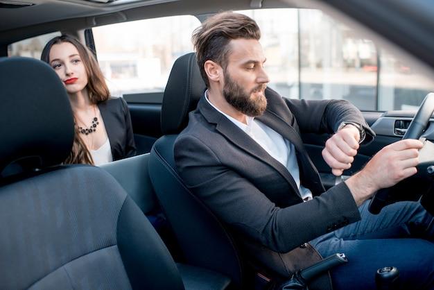 도시에서 차를 운전하는 우아한 남자와 뒷좌석에 사업가. 중요한 회의가 늦어질까 걱정된다