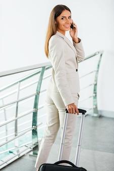이동 중에 사업가입니다. 정장 차림의 아름다운 젊은 여성 사업가가 휴대전화로 통화하고 엘리베이터에서 내리면서 웃고 있다