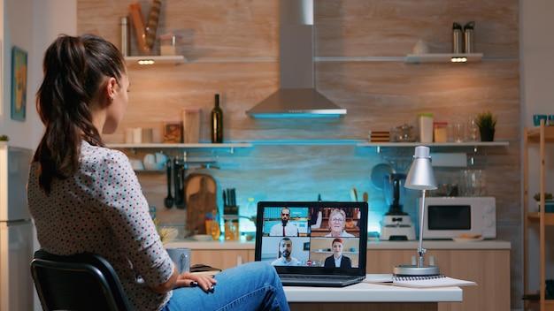 밤늦게 부엌에 앉아 집에서 원격으로 일하는 화상 회의 중인 사업가입니다. 현대 기술 네트워크 무선을 사용하여 자정에 가상 회의에서 초과 근무를 하는 여성