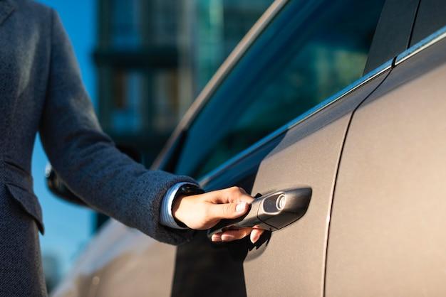 Деловая женщина, открывающая дверь машины