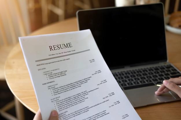 사업가 또는 구직자는 커피 숍에서 이력서를 검토하여 새로운 것을 찾기 전에 보냅니다.