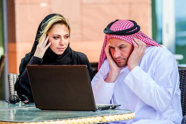 コーヒーショップでタブレットで製品を表示するアラブ人と協力して実業家または店員