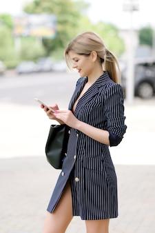 Бизнес-леди заказывает такси в приложении мобильного телефона