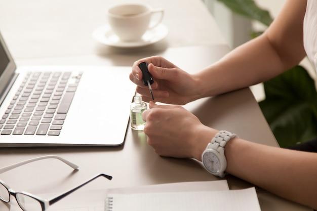 Предприниматель красит ногти в офисе