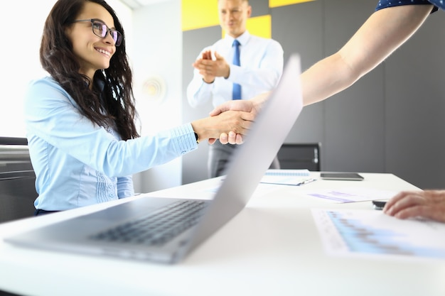 Businesswoman and partners in office shake hands and smile