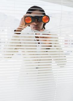 Businesswoman peeking with binoculars through blinds