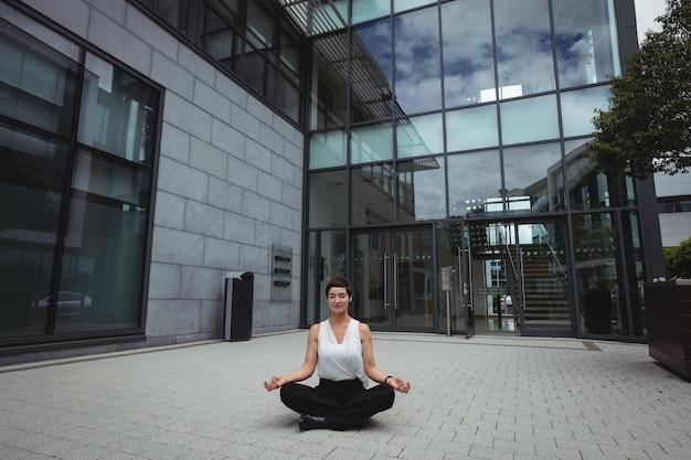 Businesswoman performing yoga