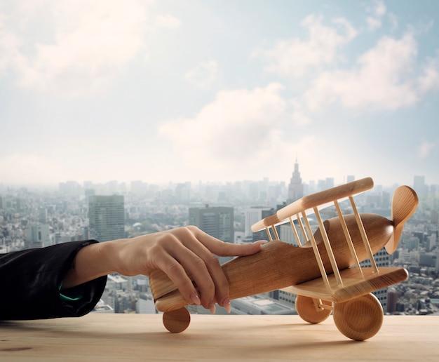 나무 장난감 항공기와 사업가 플레이. 회사 시작 및 비즈니스 성공의 개념