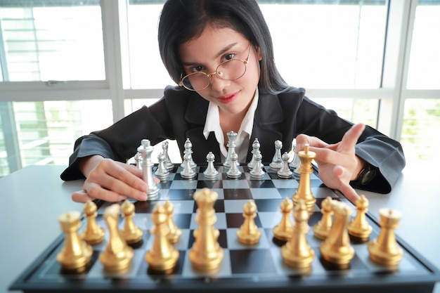 Businesswoman playing chess board game idea of management strategy and leadership.