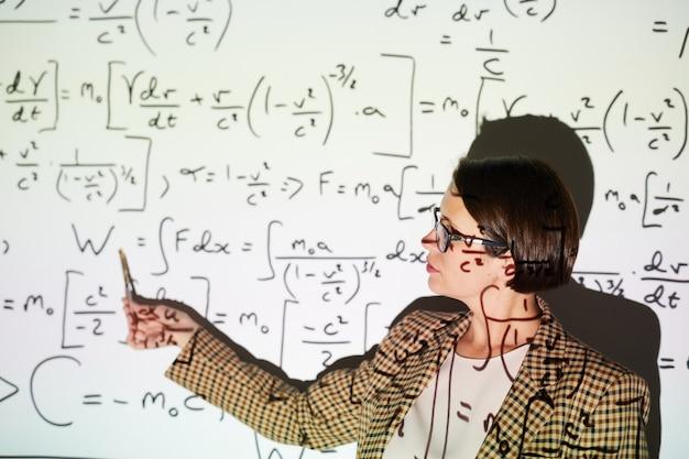 Businesswoman pointing at formulas