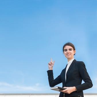 Businesswoman pointing upwards