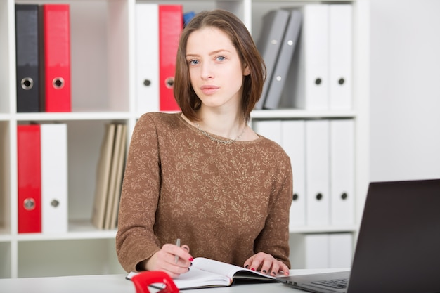 Businesswoman portrait in office using laptop and making notes