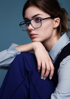 Портрет коммерсантки с стеклами и голубым костюмом. держать ее собственную руку под подбородком. ,