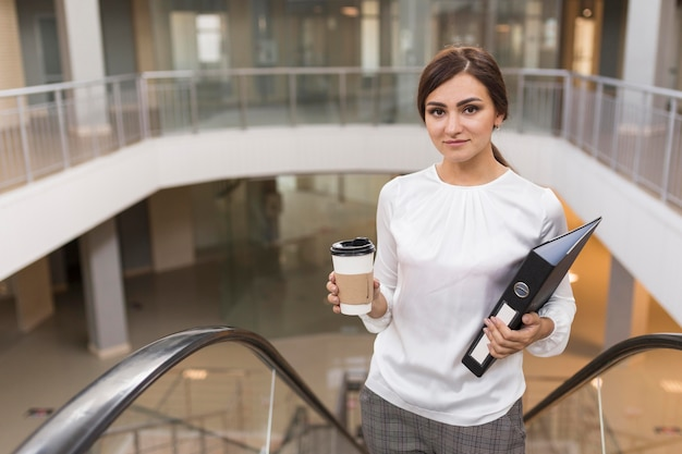 Businesswoman posing on escalator with coffee and binder