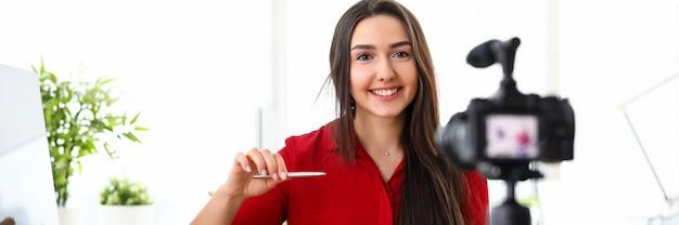 Коммерсантка представляя для камеры с ручкой в офисе