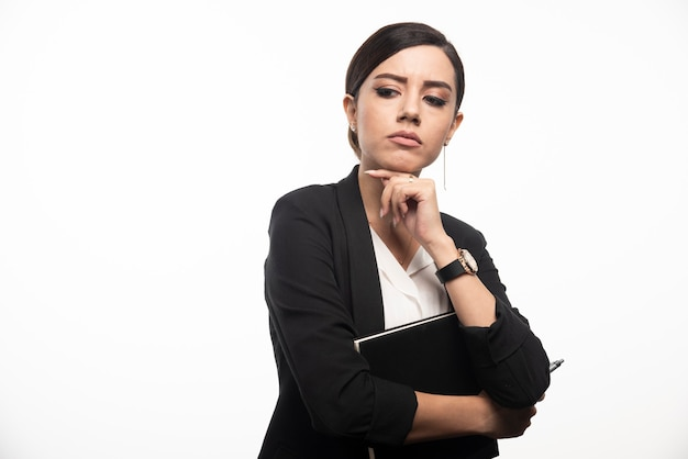 Businesswoman posing with notebook on white wall.