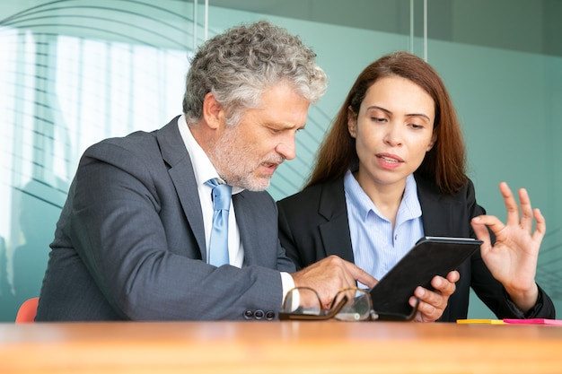 Businesswoman presenting project to investor. serious female employee showing content on tablet to colleague, explaining details.